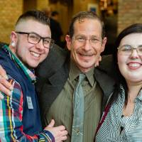 Three guests hugging and smiling at Scholarship Dinner 2019